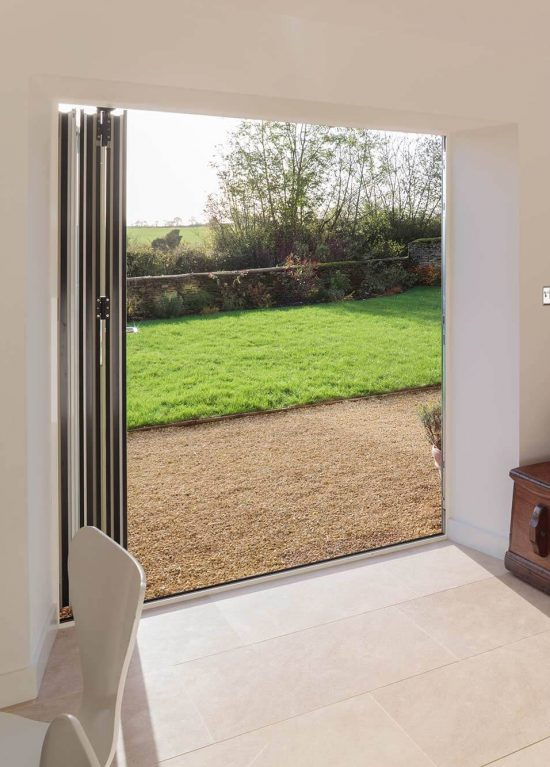 Aluminium bifolding doors fully open to reveal a wide view of the garden