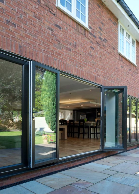 Bifold door partially open to reveal open plan kitchen