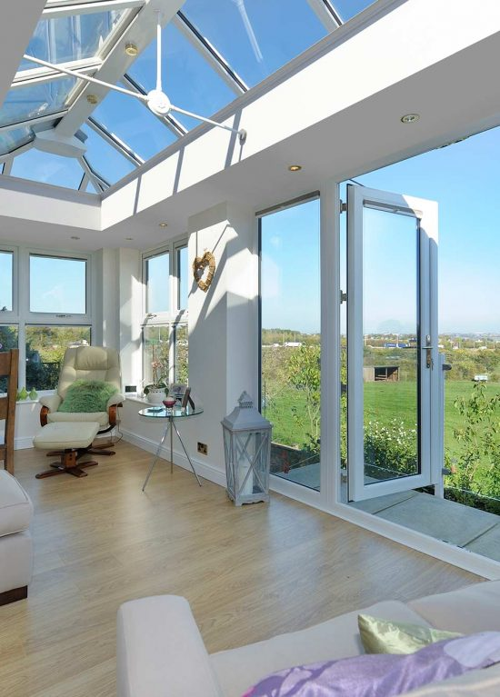 Modern glazed extension with bifolding door that open onto a view of the country