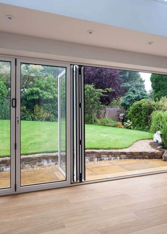 White aluminium bifold door opening onto the garden